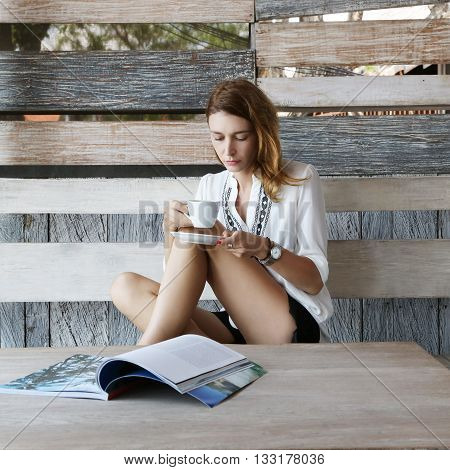 Leisure time. Young woman sipping coffee or tea and reading magazine