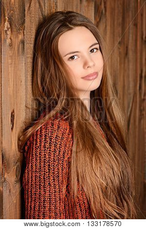 Pretty smiling teen girl in a sweater stands by a wooden wall. Modern teen generation. Youth fashion. Healthy hair, haircare.
