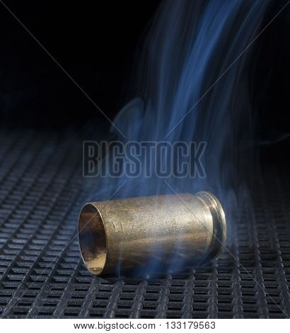 Empty brass from a semi automatic handgun on a black grate with smoke