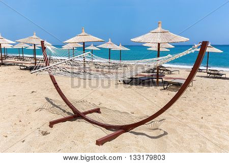 Hammock with beach umbrellas and loungers at greek coast with sea