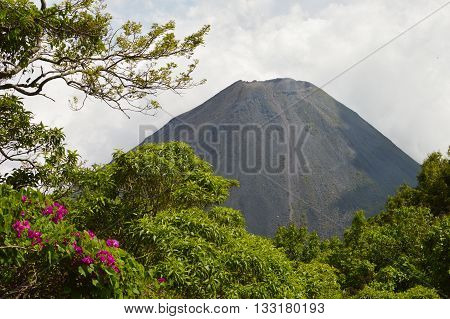 The perfect peak of the active and young Izalco volcano seen from a view point in Cerro Verde National Park in El Salvador. Nearly covered with thick white clouds.