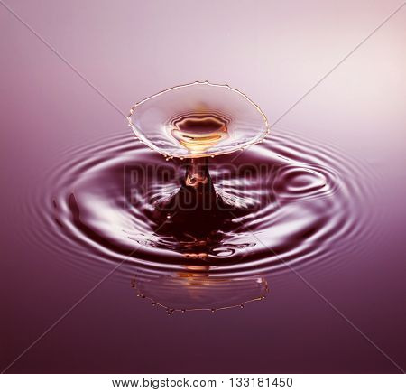 Water drop photography one or two drops of water dropped from height into water and captured as they hit the water or collide with each other.