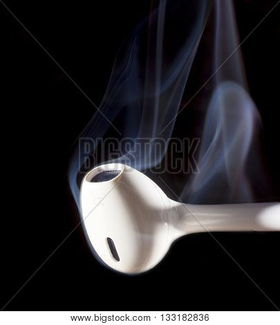 White ear phone on black with blue smoke that is rising