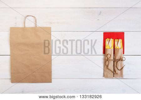Copyspace at white wooden background for menu or recipe. Food delivery, take away with brown paper bag. Food background. Fork and knife wrapped in paper, cutlery at wood, top view with copy space