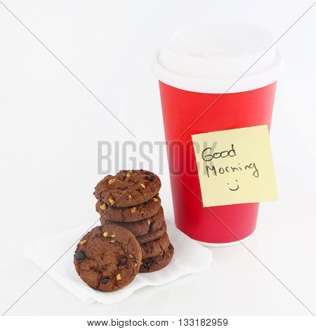Paper coffee cup with good morning note and chocolate biscuits next to it
