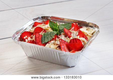 Healthy eating, diet concept. Healthy lunch, Take away organic food. Weight loss diet, food take away in aluminium box. Healthy food. Oatmeal sweet porridge with strawberries and almond slices closeup