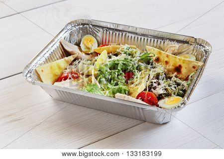 Healthy lunch box. Creative healthy food. Healthy vegetarian lunch, Take away organic food. Weight loss diet, food take away in aluminium box. Salad with parmesan, tortilla pieces and quail eggs.