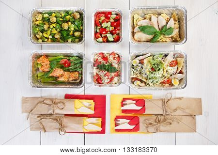 Eating right concept, healthy food. Weight loss diet, clean food take away in aluminium boxes with cutlery, vegetable salads and salmon top view, flat lay at white wood background.