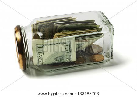 US Dollars and Coins in Glass Jar Lying on White Background