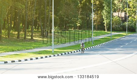 Sportsman cyclist riding racing bicycle. Woman cycling on countryside summer road or highway. Training for triathlon or cycling competition. Highway cycling