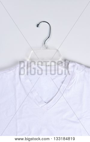 Closeup of a white tee shirt on a clear plastic hanger. Vertical format.
