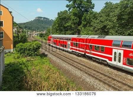 Red train is on the track in Saxony.