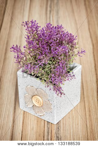 Small decorative potted plant on the wooden background. Home decoration. Beautiful house plant. Artificial flower. Vertical composition. Gardening theme.