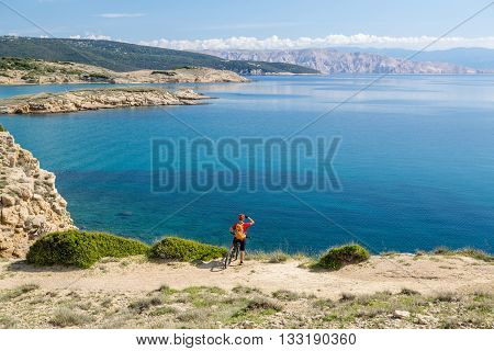 Mountain biker riding on bike in summer inspirational mountains landscape. Man cycling MTB on enduro trail track at the sea or ocean. Sport fitness motivation and inspiration.