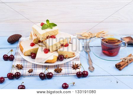 square cake with cherry on a table