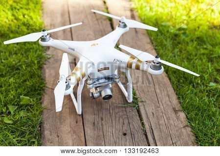 St. Petersburg Russia - May 4 2016: Drone quadrocopter Phantom 3 Professional with high resolution digital camera designed by the Chinese company DJI stands on a wooden floor close-up photo