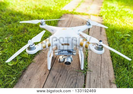 St. Petersburg Russia - May 4 2016: Drone quadrocopter Phantom 3 Professional with high resolution digital camera designed by the Chinese company DJI stands on a wooden floor closeup photo