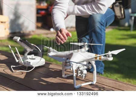 St. Petersburg Russia - May 4 2016: Drone quadrocopter Phantom 3 Professional with high resolution camera designed by the Chinese company DJI stands on a wooden floor blurred pilot on background