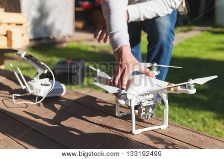 St. Petersburg Russia - May 4 2016: Drone quadrocopter Phantom 3 Professional with high resolution camera by DJI stands on a wooden floor blurred pilot and remote control on a background