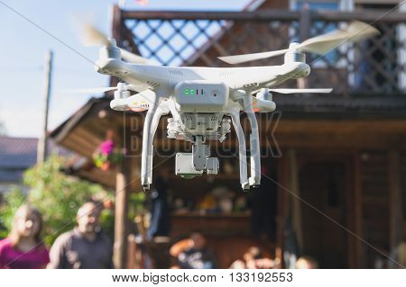 St. Petersburg Russia - May 4 2016: Drone quadrocopter Phantom 3 Professional with high resolution digital camera designed by the Chinese company DJI takes photo of group of people on a background