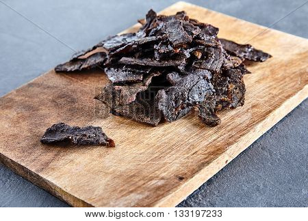 Beef jerky on wood board. Stone cement background. Thin sliced jerked or sun-dried beef with spices is a classic spicy snack for beer in pubs and bars
