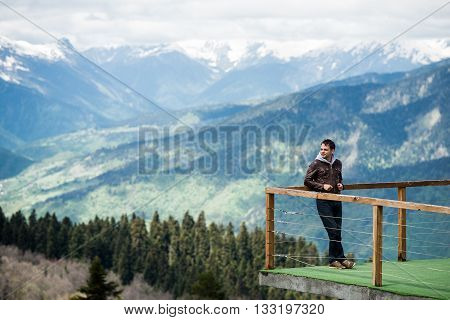 Observation deck on lookout, viewpoint in Alps mountains, Switzerland. Man standing and relaxing