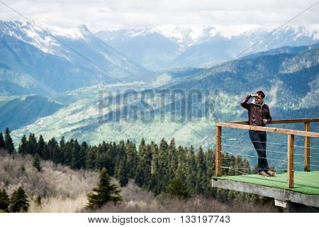 Panoramic view of green snow mountains and traveler on the mountain's viewpoint top looking sideways with hand over his eyes.