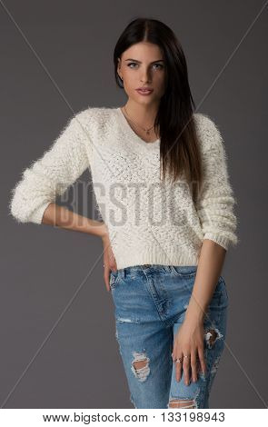 Full portrait of beautiful stylish girl on grey background. Fashion model posing at studio. Full length portrait