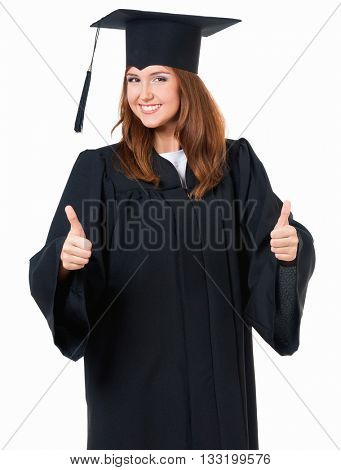 Beautiful graduate girl student in mantle showing thumb sign, isolated on white background
