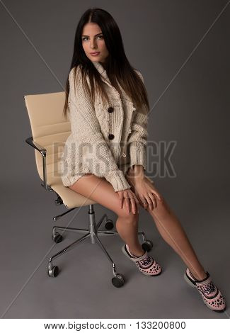 Attractive sexy brunette female with bright sweater and black stockings posing smiling sitting on office chair. Portrait of sensual fair hair woman with long legs isolated on grey background