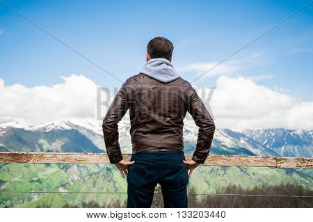 Beautiful mountains landscape with clouds and man enjoying it.