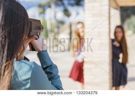 Unrecognizable photographer taking shot of two women in sunlight