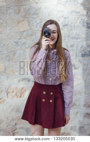 Smiling female photographer taking photo with vintage camera