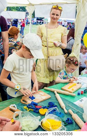 Zaporizhia/Ukraine- June 5, 2016: girls participating in pastry cooking workshop during charity family festival organized in regions with most quantity of refugees from Donetsk area, occasioned with International Children`s Day