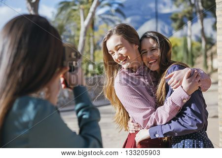 Unrecognizable photographer making photo of two smiling girlfriends outdoor