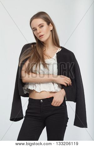 Young European attractive sexy fashion model with long blond natural hair, beautiful eyes, full lips, perfect skin is posing in black and shirt in studio for glamour vogue test photo shoot