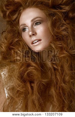 Beautiful Redhead girl with a perfectly creative curls hair and classic make-up. Beauty face. Picture taken in the studio.