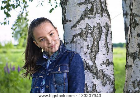 Girl standing near birch tree in summer tilting her head and smiling