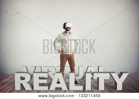 Young bearded Caucasian man in casual clothes and virtual reality glasses is standing on a sunny lawn surrounded by flying letters composing the word combination