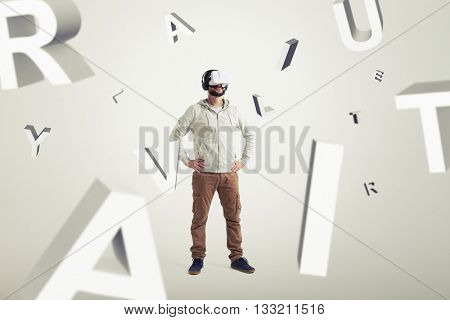 Smiling young Caucasian bearded man in casual clothes and headphones is wearing virtual reality glasses and standing surrounded by flying letters