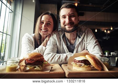A happy young couple is sitting in the burger bar, enjoying their free time and is going to eat two tasty burgers with meat and vegetables