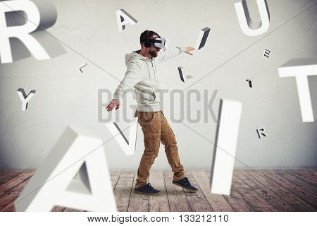 Man in virtual reality glasses is stepping carefully surrounded by flying letters composing the word combination