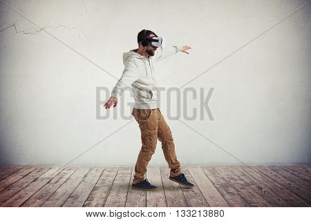 Man in virtual reality glasses is stepping carefully in white room with wooden floor