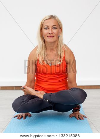 Yoga workout. Adult blonde woman doing handstand on the mat indoors