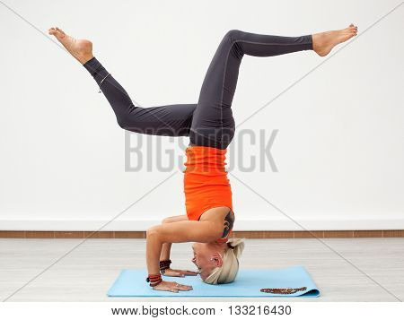 Yoga workout. Blonde woman doing handstand on the mat indoors side view