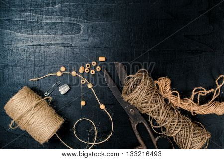 Set for needlework: scissors and skein jute twine on the black background. Top view.