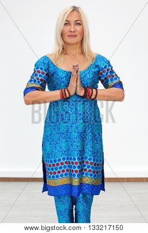 Portrait of an adult caucasian blonde woman hands are folded on the chest in the traditional asian namaste greeting