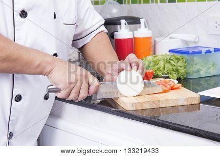 Chef cutting onion for making Hamburger / Cooking Hamburger concept