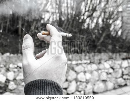 Man smoking cigarette on street black and white