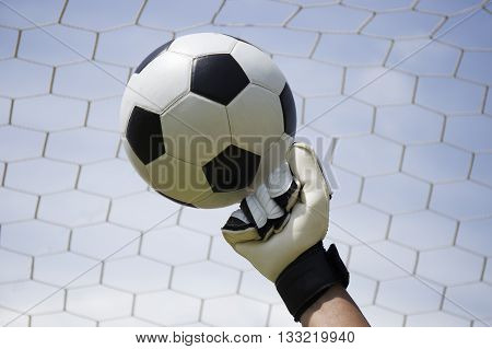 goalkeeper's hands punching a football in the goal